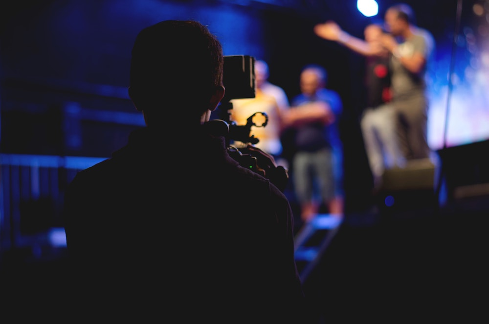 man with camera filming live event near stage